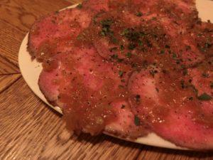 名物料理の〈低温調理した牛タンのカルパッチョ オニオンソース〉